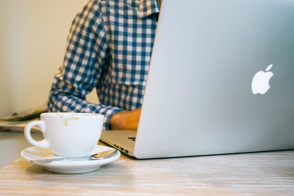 man using his mac book with a cup of coffee beside him