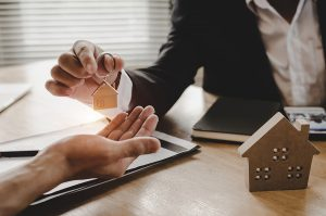 Mortgage broker giving house key to customer after signing contract
