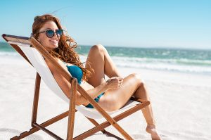 Happy woman relaxing on the beach wearing designer swimsuits