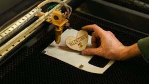 Desktop laser cutter a over a plywood sheet cut and shaped in a heart
